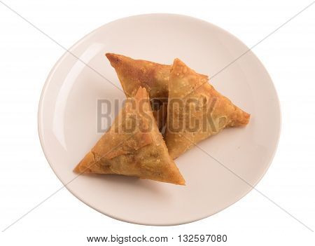 Samosas a spicy blend of vegetables or meat wrapped in a deep fried triangular pastry parcel in a white plate