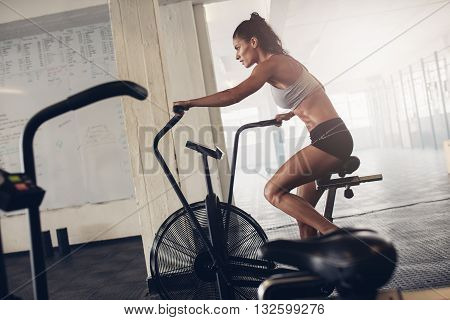 Fit Young Woman Using Exercise Bike At The Gym