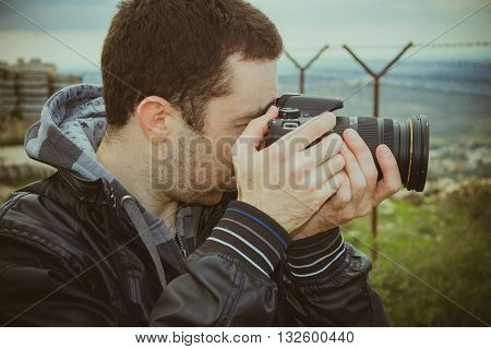 Photographer shooting outside with digital video camera.