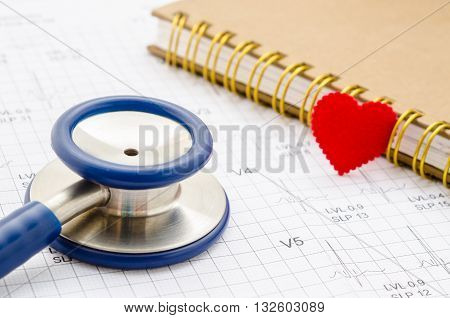 Medical stethoscope and red heart lying with diary on cardiogram chart closeup. Medical help prophylaxis disease prevention or insurance concept. Cardiology carehealth protection and prevention