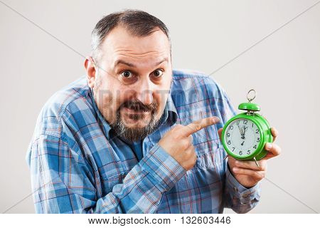 Portrait of man holding a clock that shows five to twelve time