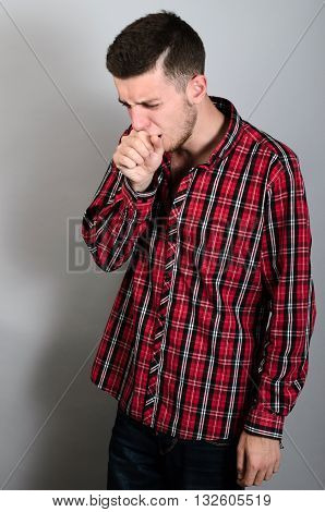 Man Coughing Into His Fist. Gray Background