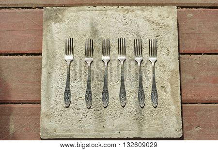 six little forks on concrete and wood floor