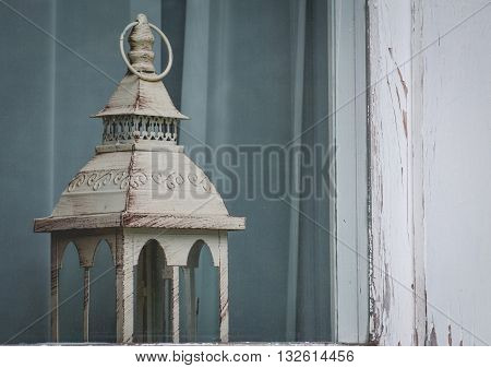 vintage lantern in the frayed window. Ancient suggestion