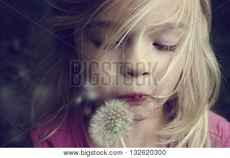 Portrait of child caucasian blond girl blowing flower dandelion seeds