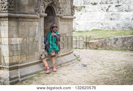 Kathmandu Nepal - March 2, 2016: A disabled needy person is showing his hand towards the Photographer while photographing him at the Temple of Pashupatinath.