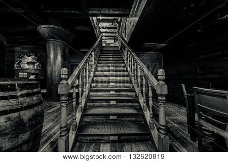 Wooden staircase. Interior of old pirate ship. Black and white image