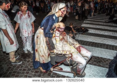 Bologna, Italy - May 21, 2016: Bologna zombie apocalypse walk: nurse zombies with zombies in a wheelchair during the parade at night.
