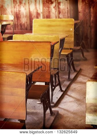 Old fashioned rustic wooden desks in a schoolhouse
