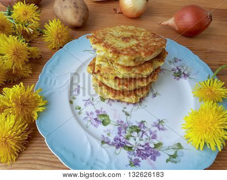 Dandelions flowers with potatoes and onion burgers on plate
