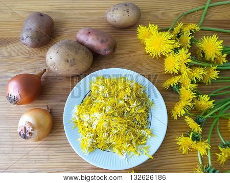 Dandelions flowers with potatoes and onion burgers cooking