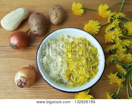 Dandelions flowers with potatoes and onion burgers cooking organic food with wild plants