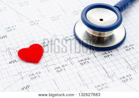 Medical stethoscope head and red toy heart lying on cardiogram chart closeup. Medical help prophylaxis disease prevention or insurance concept. Cardiology care health protection and prevention