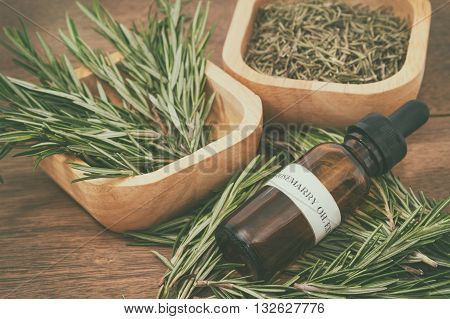 Rosemary essential oil in bottle and fresh rosemary on old wooden background