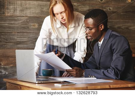 Corporate business colleagues of different races working together on laptop. Caucasian businesswoman and African entrepreneur having discussion at the cafe while drinking coffee during lunch break