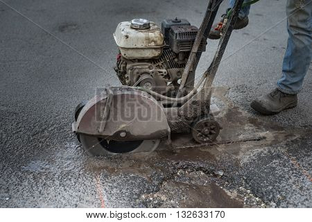 Worker cuts a piece of asphalt using a cutting machine pavement. The machine for cutting asphalt. Pothole on the road. poster