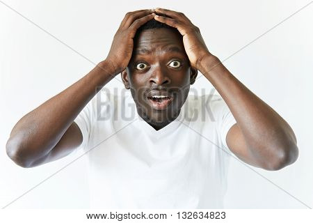 Portrait Of Shocked Young African American Man Wearing White Blank T-shirt Looking At The Camera In