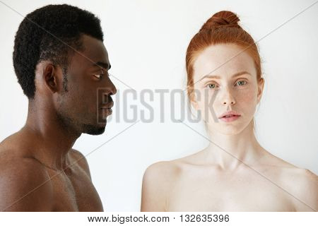 Coffee And Milk. Portrait Of Young Multi-ethnic Couple Posing Naked Against White Studio Wall. Profi