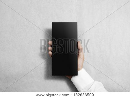 Hand holding blank black flyer brochure booklet in the hand. Leaflet presentation. Pamphlet hold hand. Man show grey offset paper. Sheet template. Booklet design. Paper sheet display read first person