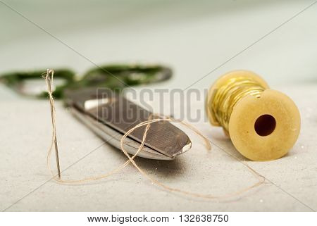 Sewing textile or cloth. Work table of a tailor. Textile tools. Scissors reel of thread, measuring tapes and natural fabric.