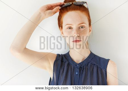 Pretty Young Female With Ginger Hair And Green Eyes In Spotted Dress, Wearing Sunglasses On Her Head