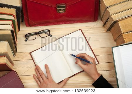 Follow the law. Professional lawyer sitting at the table and signing papers. On a wooden table books, documents, glasses, red briefcase.