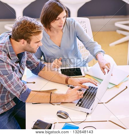 male and female business partners working together early in the morning on a laptop and tablet in a public co-working space