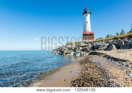 Stony Lake Superior Beach with Crisp Point Light in the background. poster