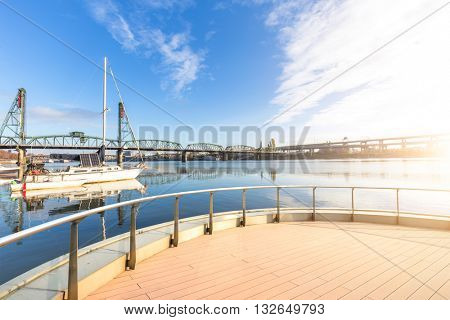steel bridge over water and sail boat in portland at sunrise in blue sky on view from empty brick floor