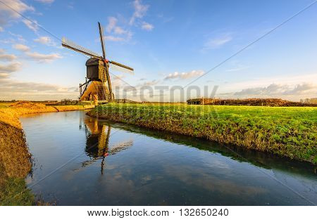 Historic Dutch wooden post polder miil reflected in the mirror smooth water surface covered with a thin layer of ice. It's winter now.