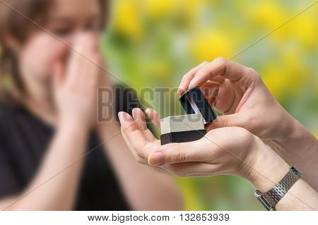 Wedding proposal concept. Man holds box with wedding ring in hands and is proposing to a surprised woman.
