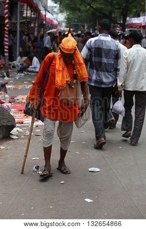 Pune India - July 11 2015: An old pilgrim known as warkari walking down the road during the famous Wari festival in India.