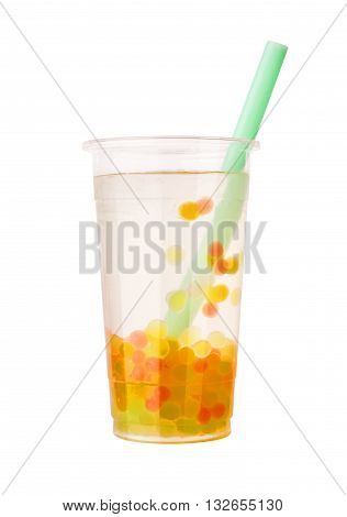 Clear bubble tea with orange, red and yellow tapioca with a straw isolated on white