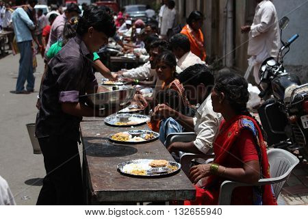 Pune India - July 11 2015: Indian pilgrims known as warkaris been served free meal on the side of the road during Wari festival in India.