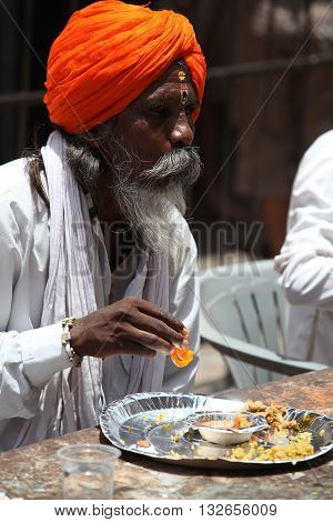 Pune India - July 11 2015: A hindu pilgrim having a meal served to him by a charitable organization during the Wari festival in India.
