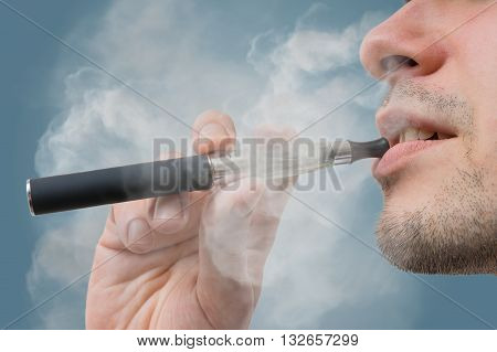 Man holds vaporizer and is smoking e-cigarette.