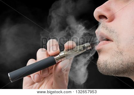 Man Holds Vaporizer Or E-cigarette In Hand And Vaping.