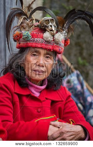 BANAUE PHILIPPINES - JANUARY 24 2014 : Portrait old Filipino woman of Ifugao mountain tribes in national dress next to rice terraces. Ifugao - the mountain people in the Philippines.