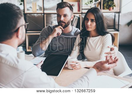 They need expert advice. Young couple sitting together at the desk and listening to their financial advisor