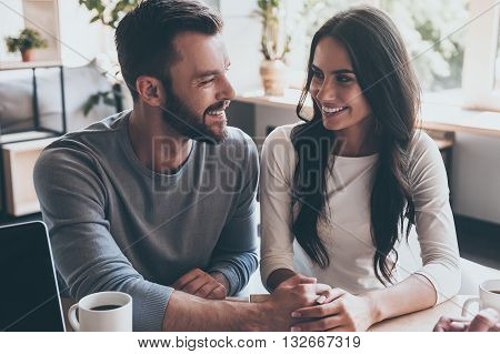 Feeling happy now. Happy young loving couple holding hands and looking at each other while sitting at the desk with some man sitting in front of them