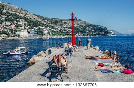Dubrovnik Croatia - August 26 2015. Tourists at Porporela pier and breakwater on the end of Old Town Harbour in Dubrovnik