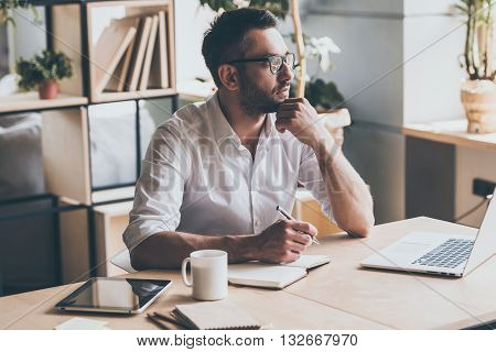 In search of inspiration. Thoughtful mature man holding pen and looking away while sitting at his working place in office