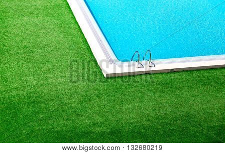 Beautiful swimming pool with green grass around.Lovely pool in the garden in the park.Swimming pool of luxury hotel.Swimming pool with blue clear water.