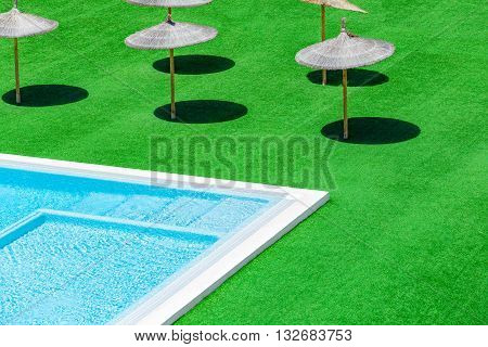 Swimming pool green grass and straw umbrellas with shadow. Sun umbrellas with shadow from the sun. Beach umbrellas near the swimming pool.