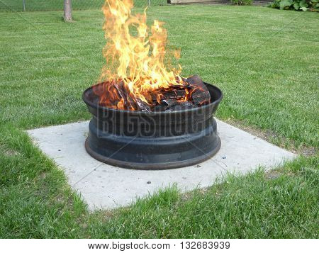 A backyard fire pit sitting on concrete slab I made from a semi truck tire rim.