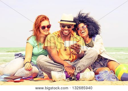 Multiracial friends having fun watching travel video at the beach - Happy group of students using mobile phone by the ocean - Concept of friendship and new technologies - Nostalgic vintage filter look