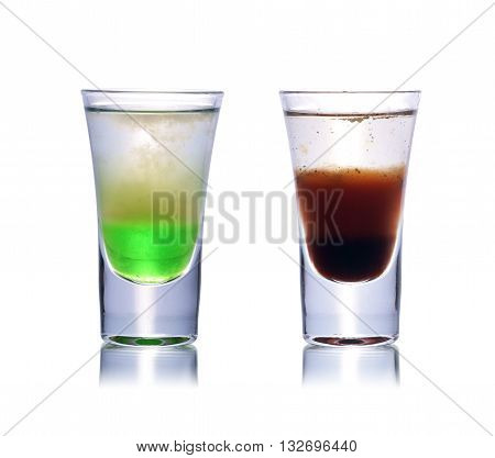 Set of colorful alcoholic cocktails in shot glasses isolated on white with reflection. Colletion of shooters