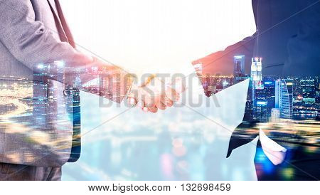 Closeup of businessmen shaking hands on illuminated night city background. Double exposure