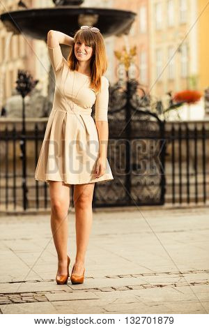 Holidays and tourism concept. Full length pretty woman in elegant dress outdoor on the street of old town european city Gdansk Danzig Neptune fountain Poland