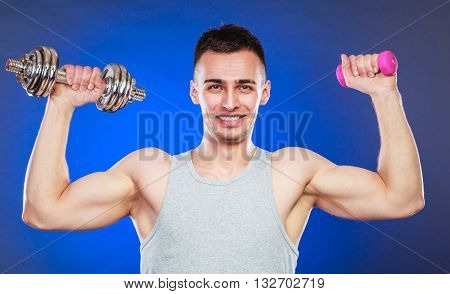 Sporty fit man lifting light and heavy dumbbells weights. Young muscular strong guy training. Bodybuilding exercise. poster